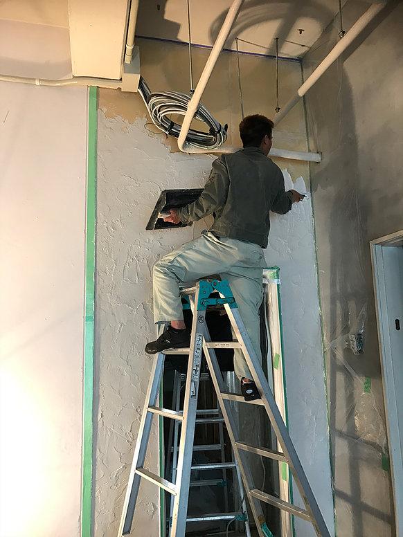 脚立で壁を塗っている写真